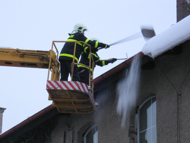 Odstraňování sněhu z budovy firmy J-4